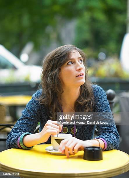Woman having coffee at sidewalk cafe