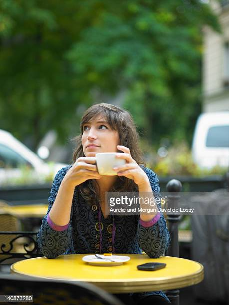 Woman having coffee at sidewalk cafe
