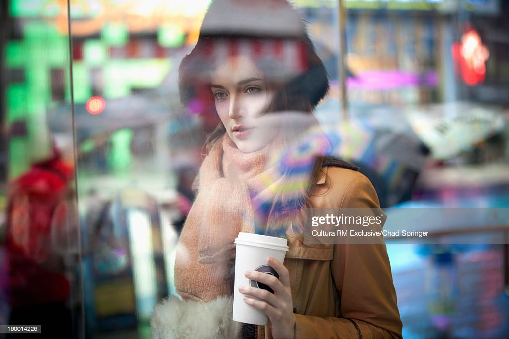Woman having coffee on city street : Stock Photo