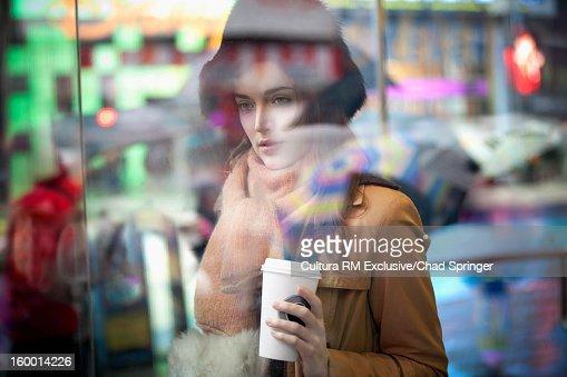 Woman having coffee on city street : Stock Photo