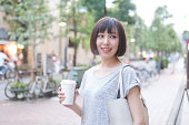 Woman having coffee on street,smiling
