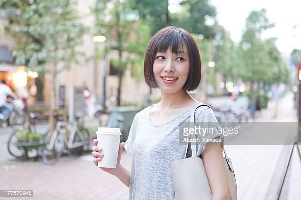 Woman having coffee on street,smiling