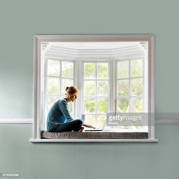 Woman having coffee while using laptop on window sill