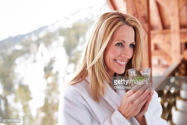 Woman having drink on cabin balcony