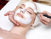 Beautiful young girl with facial mask at beauty salon