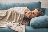 Exhausted woman having fever and blowing nose.Image is intentionally toned.