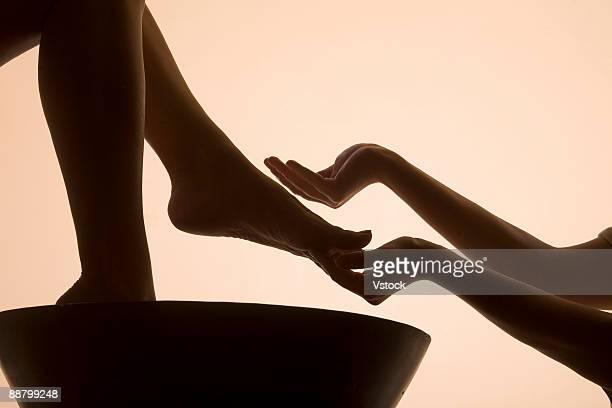 Woman having foot bath in spa, low section