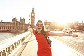 Woman having fun at sunset at Westminster bridge