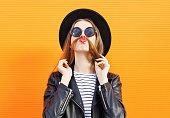 Woman having fun shows moustache hair over orange background