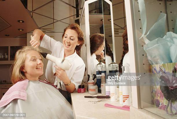 Woman having hair done by hairdresser in salon
