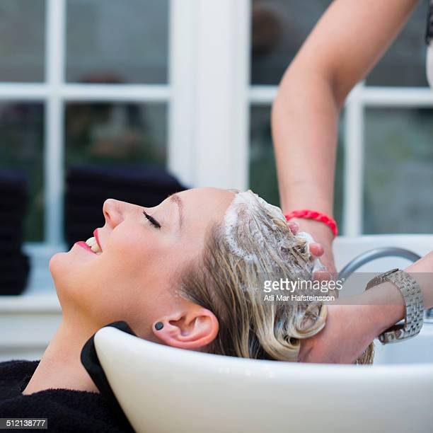 Woman having hair shampooed in salon