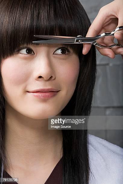 Frau, die Ihr Haar schneiden
