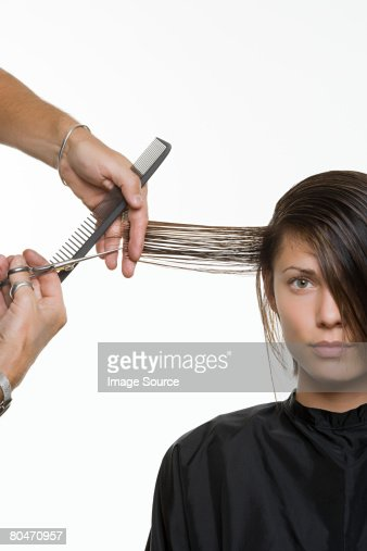 A woman having her hair cut : Stock Photo