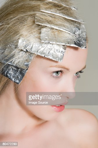A woman having her hair highlighted : Stock Photo