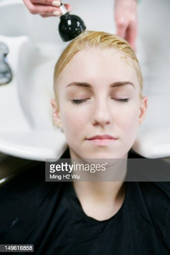 Woman having her hair washed in salon : Stock Photo