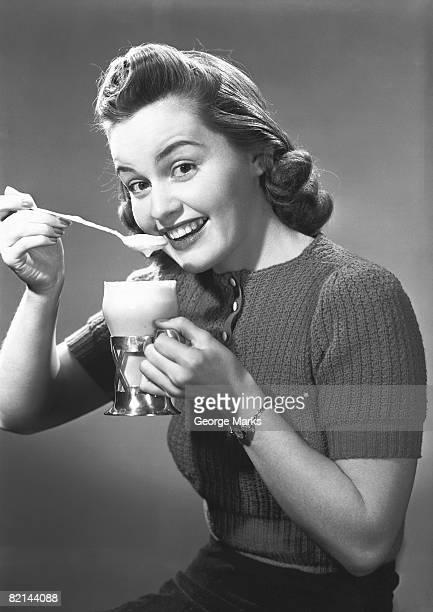 Woman having ice cream soda in studio, (B&W), portrait
