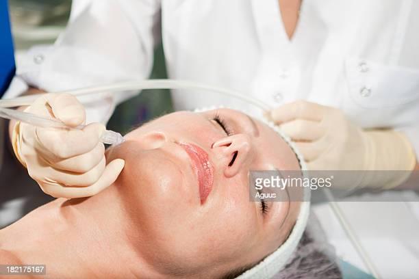 Woman having jet peeling facial treatment