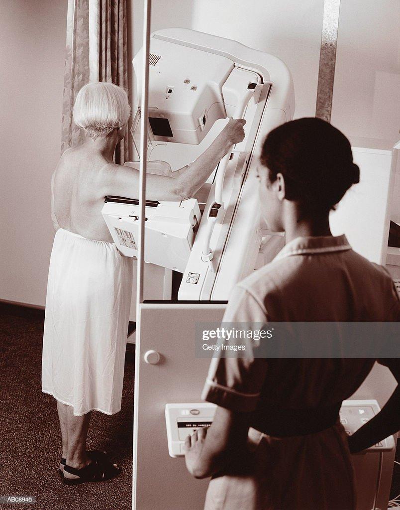 Woman having mammogram, technician in foreground