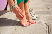 Clos-up photograpfy of woman having painful feet due to unfit shoes