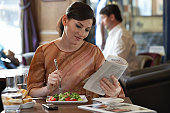Woman having pub lunch, eating salad and reading magazine