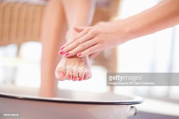 Woman having salt scrub on feet