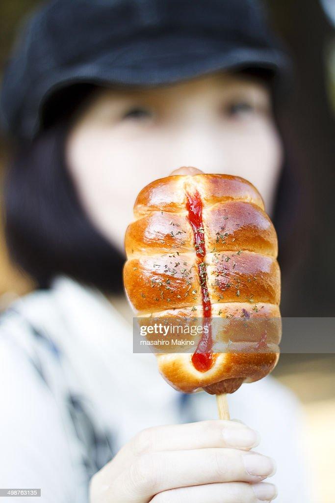 Woman Having Sausage Bread : Stock Photo