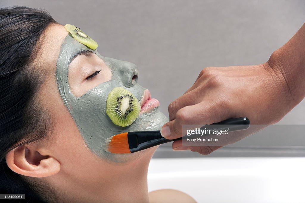 Woman having skin mask applied in bath : Stock Photo