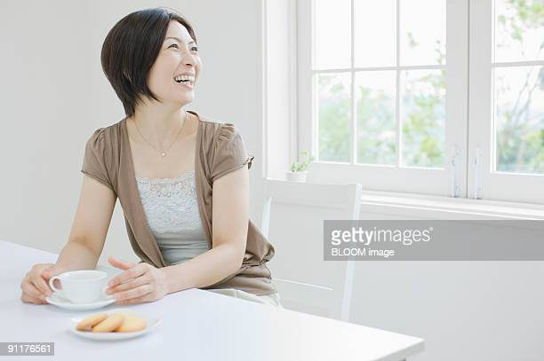 Woman having tea, smiling