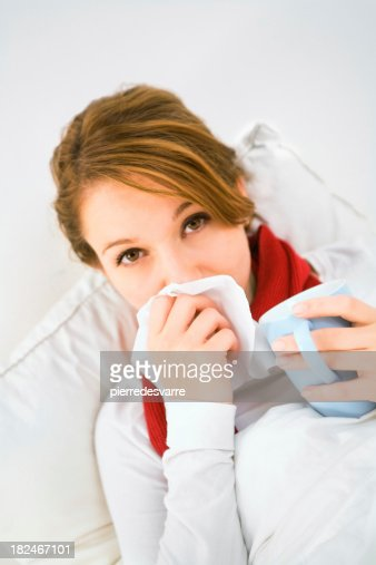 Woman having the flu drinking tea and blowing nose