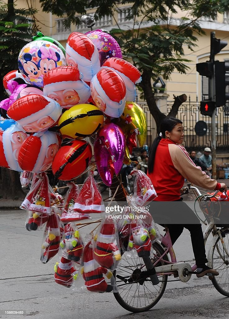 A woman hawks Santa Claus dolls, balloons and Christmas hats as she rides her bicycle along a street in downtown Hanoi on December 21, 2012. Churches, shops, restaurants and shopping mails are being decorated in the Southeast Asian communist nation where some 6 million catholic community are preparing to celebrate Christmas. AFP PHOTO/HOANG DINH Nam
