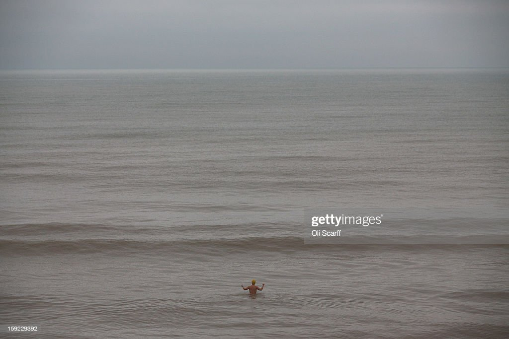 A woman heads out to sea for a swim from Brighton beach on January 9, 2013 in Brighton, England.