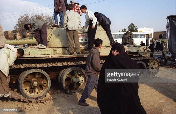 A woman heads towards the grave of her son while children play on a captured Iraqi tank on display in Beheshte Zahra cemetery Tehran where thousands...