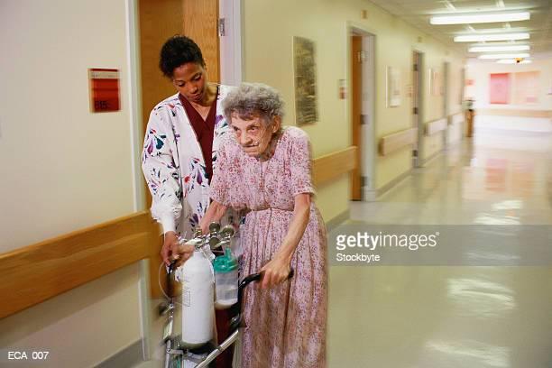 Woman helping elderly woman with walker down corridor