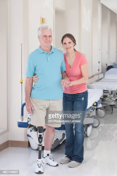 Woman helping father walk with prosthetic leg in hospital