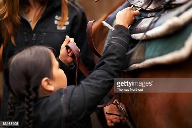Woman helping girl saddle horse