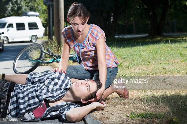 Woman helping injured man lying on roadside