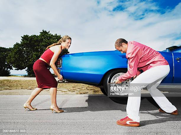 Woman helping man change car tyre at side of road, trying to lift car