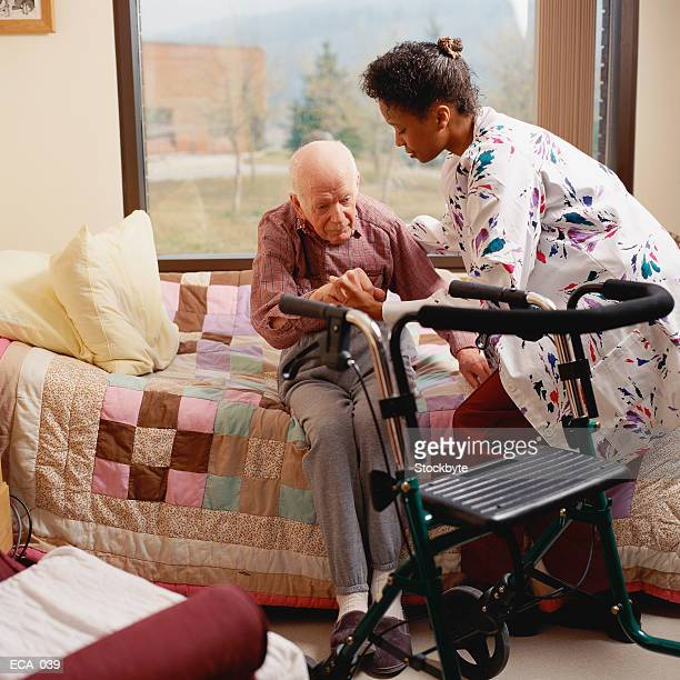 Woman helping man off bed, walker in front of him