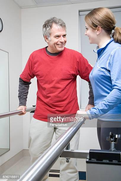 Woman helping man walk on crutches in hospital