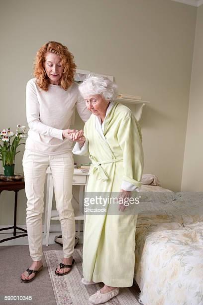 Woman helping mother walk in bedroom