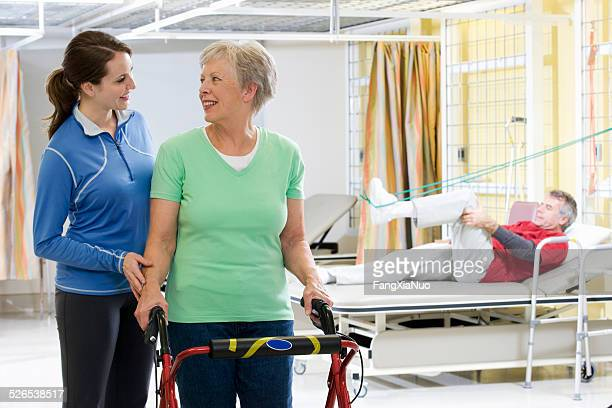 Femme aidant femme marche dans le centre de réhabilitation