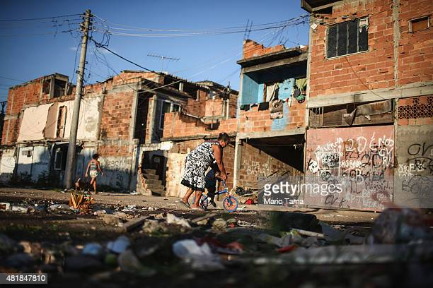 A woman helps a child ride a bike amidst the rubble of destroyed homes in the MetroMangueira community or 'favela' located approximately 750 meters...