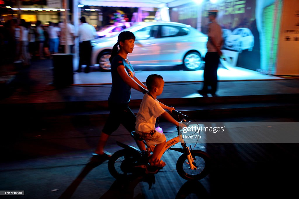 A woman helps her child to ride bicycle as they enjoy the coolness in the night on August 4, 2013 in Chongqing, China. Chongqing is a major city in southwest China and became the municipality was created on 14 March 1997. It known as a 'Mountain City' and 'River City' was constructed on the mountain and along the Yangtze River.