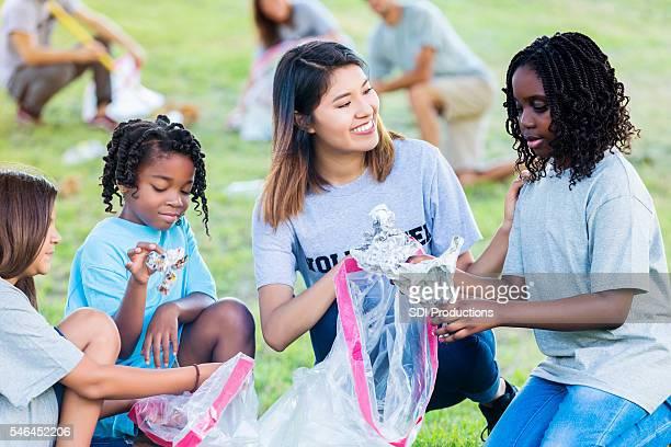 Woman helps kids clean up park