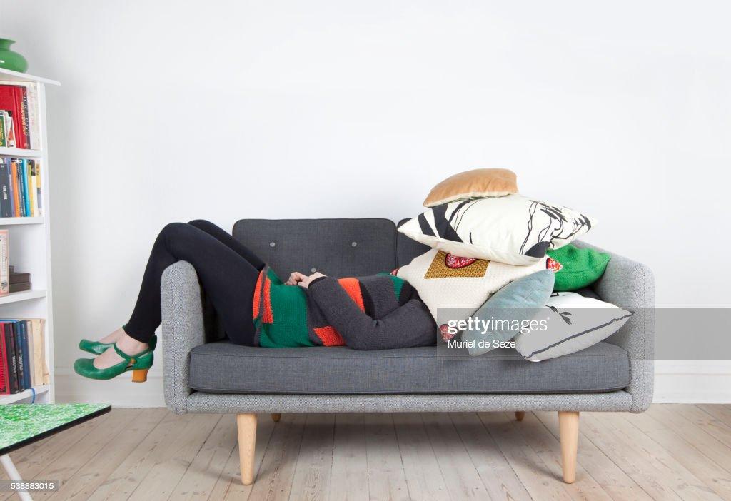 Woman hidden by pillows