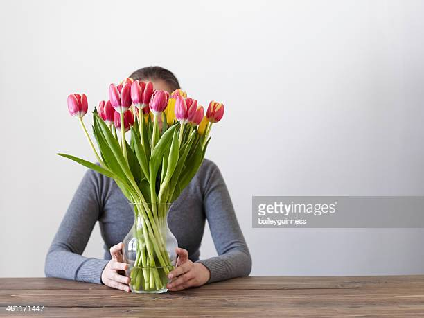 Woman hiding behind flower at a table