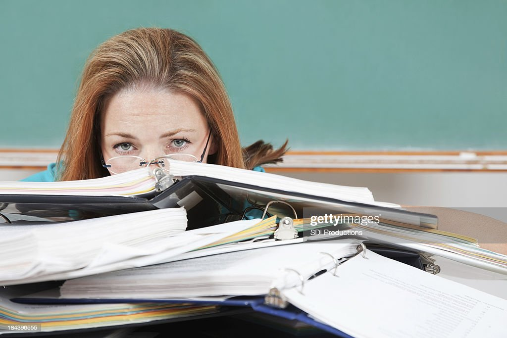 Woman hiding behind school binders in classroom : Stock Photo