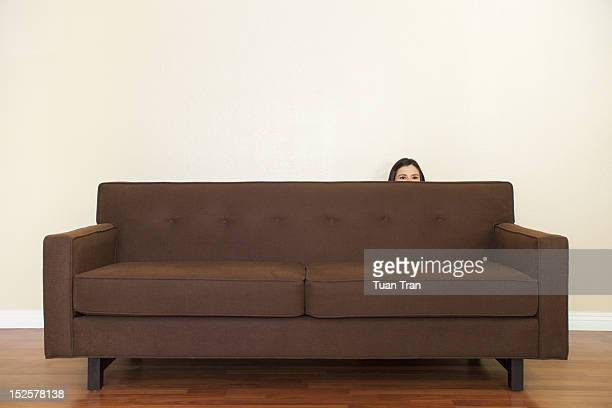 Woman hiding behind sofa
