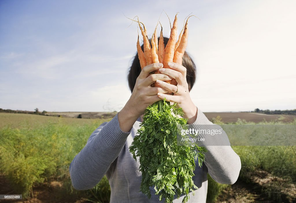 Woman hiding face behind carrots : Stock Photo