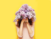 Woman hiding head in bouquet lilac flowers over yellow background